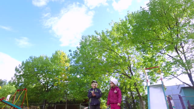 Blond boy and girl with glasses start flying chopper. Children play on the playground and laugh. video