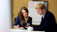 Blond businessman in glasses explains businesswoman task meeting video