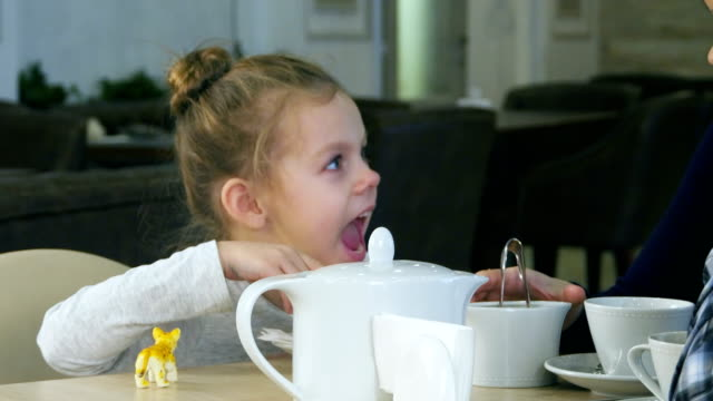 Blond cute girl tries to put sugar in her cup of tea. Her mother helps her video