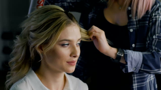 Blond female in hair salon. Hairdresser on background video