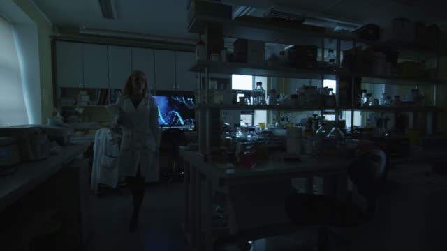 Blond female scientist is coming to the laboratory and turning the lights on. video