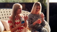 Blond friends sip drinks colored red and blue video