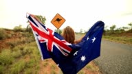 Blond girl holding Australian flag in air near Kangaroo sign video