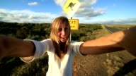 Blond girl traveling takes selfie with kangaroo crossing sign video