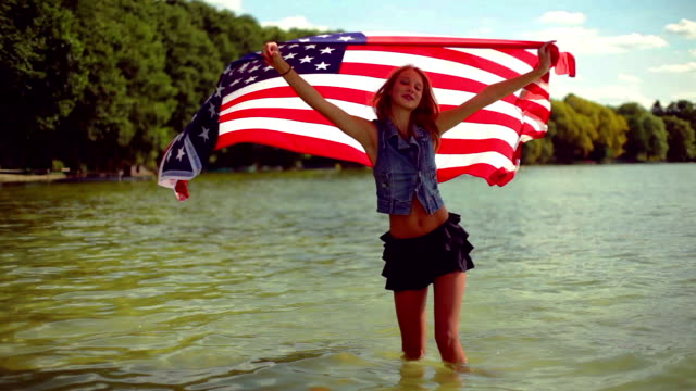 Blond girl waving American flag in the lake. video