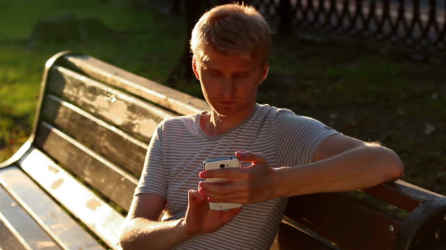 Blond male writing sms message to girlfriend sitting in park video