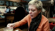 Blond short hair woman eats and talk to a friend video
