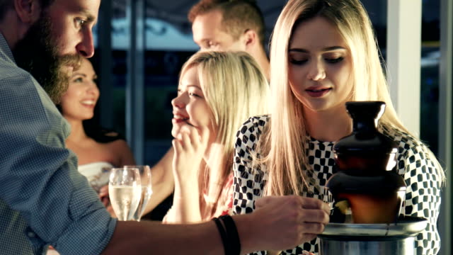 Blond woman dipping fondue with man video