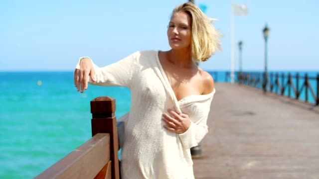 Blond Woman in White Cover Up Standing on Pier video