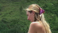 Blond woman reading a book in the green; backzoom video