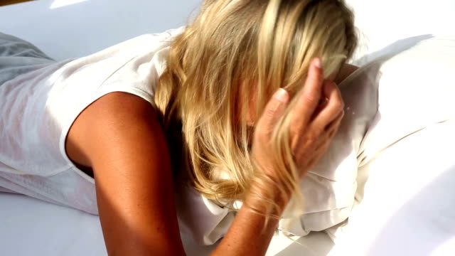 blond woman waking up on sunny morning and doesn't want to get up video