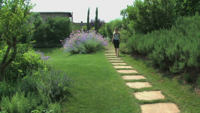 Blond woman walking in a marvelous flowered Tuscan garden video