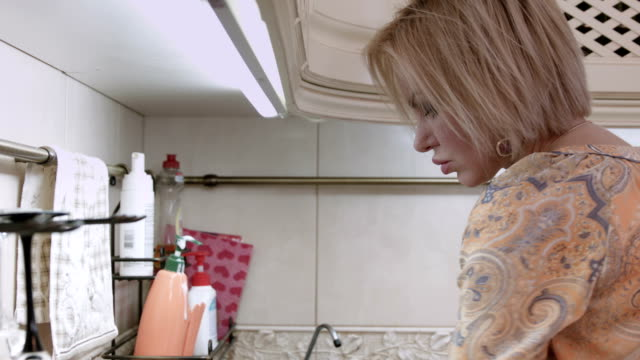 Blond woman washes the plates video