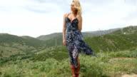 Blond Woman Wearing Dress on Hill near Wind Farm video
