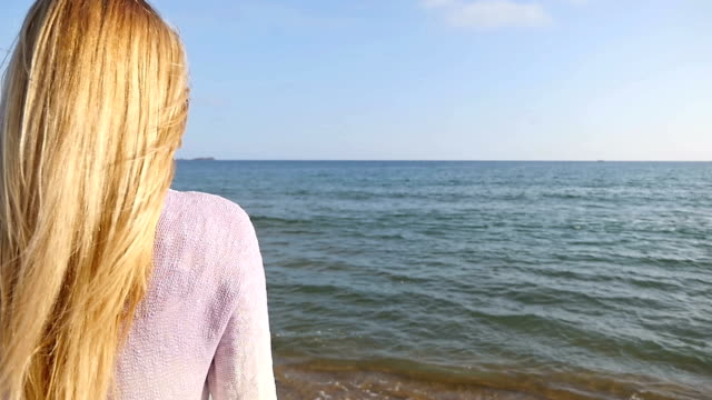 Blond young woman looking at sea view video