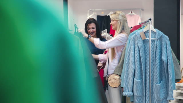 Blonde and brunette discussing clothes in the store. Shopping woman video