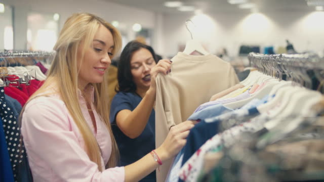 Blonde and brunette looking for clothes with clothes on video