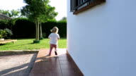 blonde baby running from door house to garden video