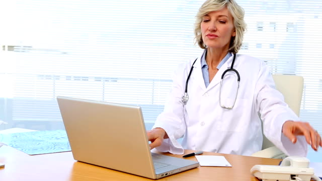 Blonde doctor working at her desk video