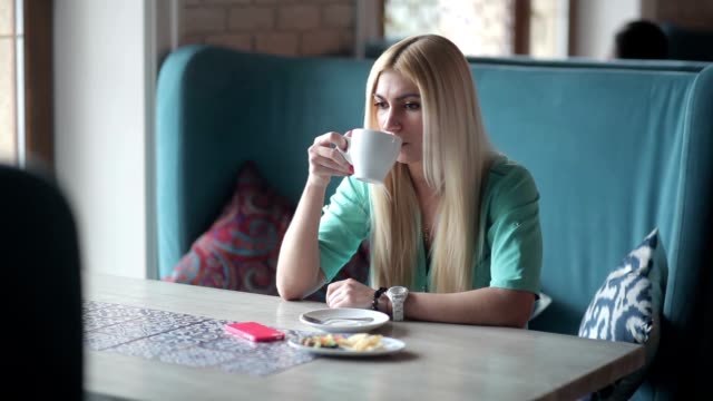Blonde drinking coffee and looking at her watch. video