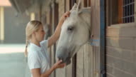 SLO MO DS Blonde female feeding white horse in stable video
