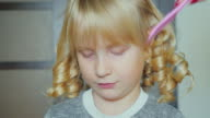 Blonde girl 5 years wind the hair using curlers video