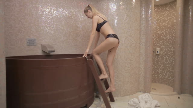 Blonde girl come to the bath with cold water after sauna video