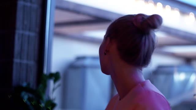 Blonde girl dancing at sofa on party in nightclub. Cheering. Smile, sing video