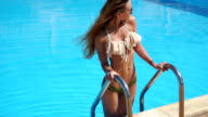 blonde girl in seductive swimsuit posing by the pool video