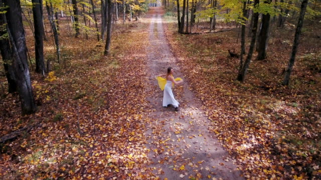 Blonde girl in white dress dancing in fall leaves video