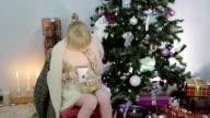 Blonde girl is drinking tea near the Christmas tree. video