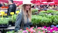 Blonde girl looking at flowers in market video