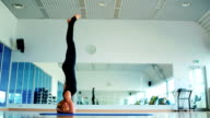 Blonde girl standing on the head and training the yoga in the sport's gym video