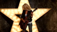 blonde girl with electric guitar in leather, shining star in the background, slow motion video