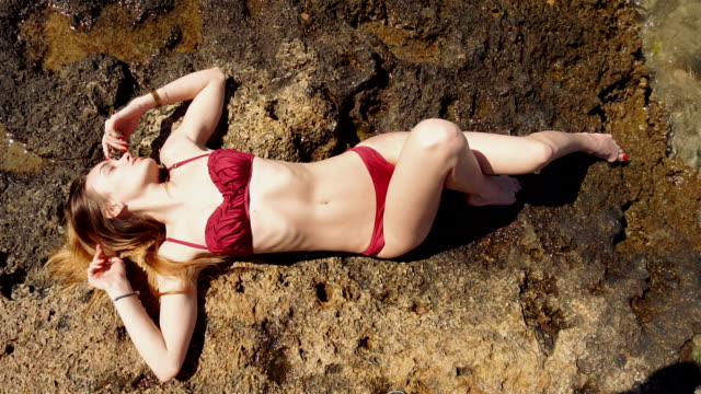 blonde lady in red swimsuit lying on the rock and sunbathing video