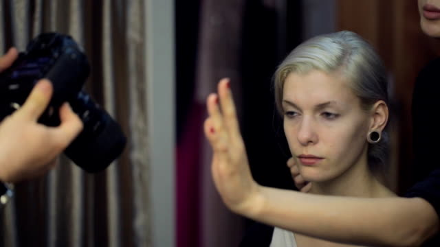 Blonde model sits in dressing room and looks at photographer video