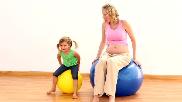 Blonde pregnant woman sitting on exercise ball with little girl video