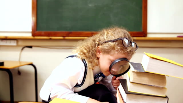 Blonde pupil using magnifying glass video