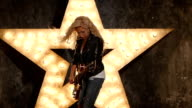 blonde rock girl with electric guitar in leather, shining star in the background, slow motion video