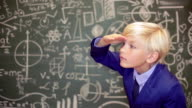 Blonde teenage boy behind a blackboard with telescope video
