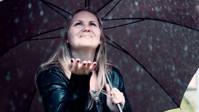 Blonde woman enjoying rain under black twisting umbrella video