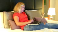 Blonde woman lying on a bed using laptop video
