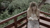 Blonde woman reading a book video