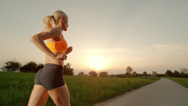 SLO MO TS Blonde woman running at sunset video