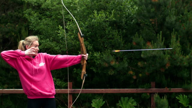 Blonde woman shooting bow and arrow in cinemagraph video