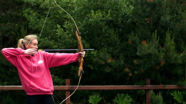 Blonde woman shooting bow and arrow video