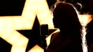 blonde woman Singing with Retro Microphone, slow motion, close up, silhouette video