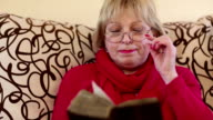 Blonde woman sits on a sofa and reads ancient book video