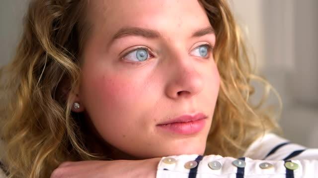 Blonde woman staring through the window video
