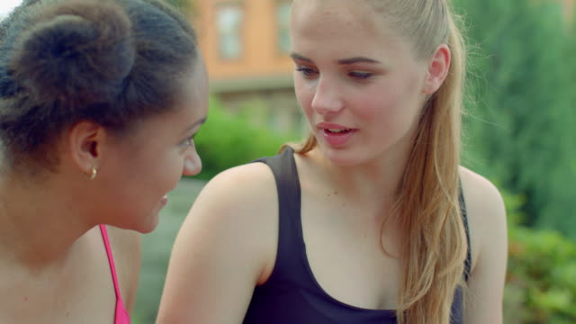 Blonde woman talking with african girlfriend outdoor. Multiracial friends video